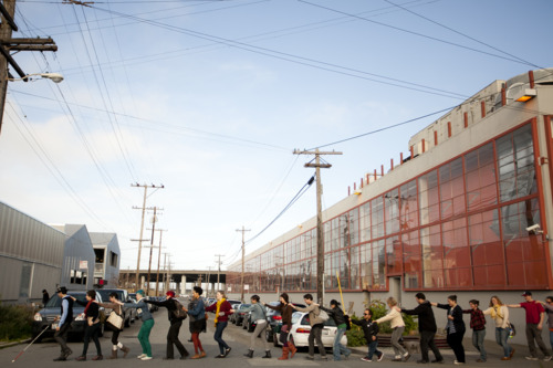 Carmen Papalia leads groups of up to 50 people through California urban spaces for The Blind Field Shuttle. This horizonal image shows a long queue crossing an industrial area.